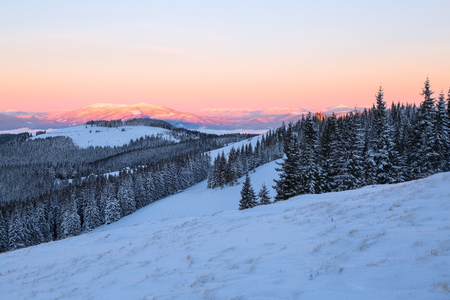 Landscape with high mountains covered with snow. Interesting frozen texture. Beautiful winter sunrise with orange and pink blue sky. Place for tourists. Christmas story.