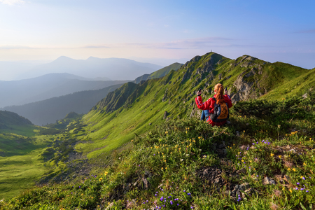 Among the wild mountains flowers at the edge of the cliff there is a girl sitting and watching the peaks of mountains at the horizon. Rocky mountains. Stockfoto
