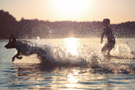 Beautiful summer landscape. A kid is playing with a dog in lake. Water splashes . sunset. Happy childhood.