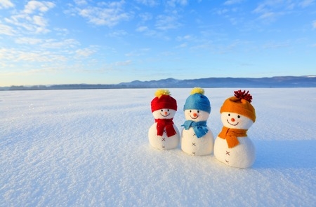 Three small snowman in colorful hats are standing on the snow. The scenery with mountains, field in snow, blue sky. Beautiful winter day. Stok Fotoğraf