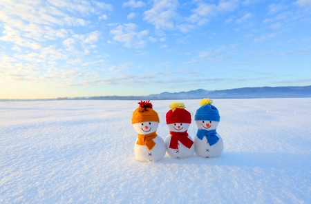 Friends snowman in red, blue, yellow hats and scarfs. Nice winter scenery with mountains, field in snow. Orange sunset background.
