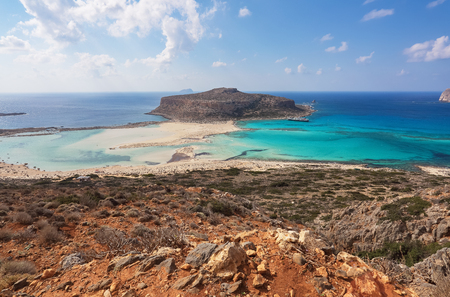 Scenery of sunny summer day with sand beach, turquoise sea and mountains. Blue horizon line. Place for tourists rest Balos lagoon, shore of Crete island, Greece. Ionian, Aegean and Libyan seas. Stockfoto
