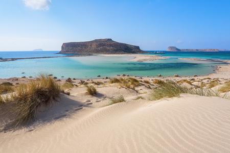 Scenario di soleggiata giornata estiva con spiaggia di sabbia, mare turchese e montagne. Linea dell'orizzonte blu. Posto per i turisti resto laguna di Balos, riva dell'isola di Creta, Grecia. Mar Ionio, Egeo e Libico.