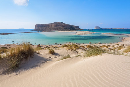 Scenery of sunny summer day with sand beach, turquoise sea and mountains. Blue horizon line. Place for tourists rest Balos lagoon, shore of Crete island, Greece. Ionian, Aegean and Libyan seas. Stock Photo