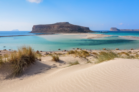 The white sand beside the sea, where the bottom can be seen, the beach with people. Beautiful mountains on a blue horizon. Incredible Balos. A landscape on a summer sunny day. Crete Island, Greece.