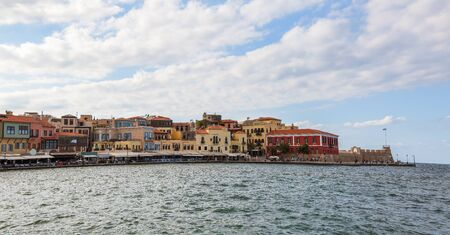 A panorama of the harbor city of Chania. View of the emarald sea, interesting landscapes, colorful houses, a coast view from the cafe. The Mediterranean Sea. A popular tourist resort in the Greece