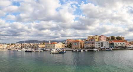 A panorama of the seaport town Chania, the island of Crete, Greece. A harbor with wooden pantons, moored yachts, ships, boats. Colorful architecture of modern and old houses. Mountains on the horizon