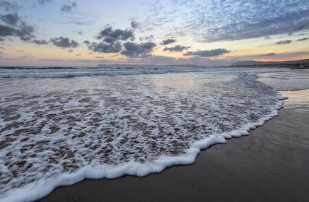 Onde alte con schiuma spalmate sulla sabbia della costa. La luce dell'incredibile tramonto si riflette sul mare. Orario prima dell'alba. Bello illuminare il cielo con le nuvole. Montagne. Luogo di relax romantico.