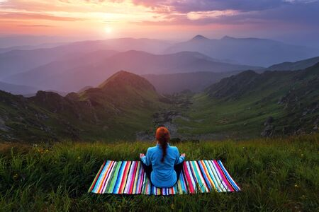 The girl on colorful mat is practicing Yoga. Beautiful mesmerising sunrise, orange sky with clouds, high mountains in fog. Perfect summer morning for meditation. Location Carpathians, Ukraine, Europe. Archivio Fotografico