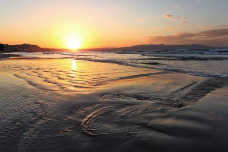 Location place Agia Marina Beach, island Crete, Greece. Sea coast spangled by rocks, the sunrise is reflecting on the wet sand. The mountains in haze on the horizon. Storm sea with high waves. Imagens