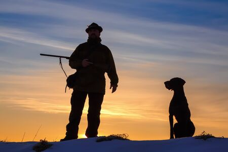 A hunter in the hat with a gun and his German Shorthaired Pointer dog breed friend. Beautiful silhouettes on the background of the dawn. Amazing winter morning. Imagens
