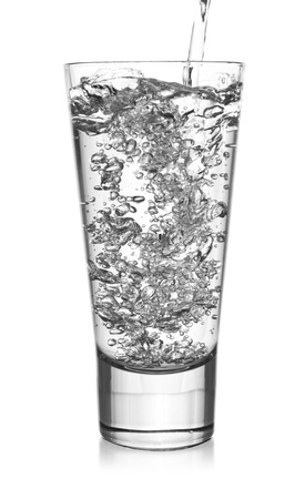 Strong pouring of water into the glass with bubbles Stock Photo