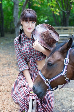 Pretty cowgirl spending time with horses
