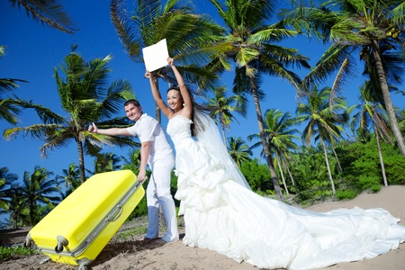 Newlyweds are hitchhiking at a tropical location photo