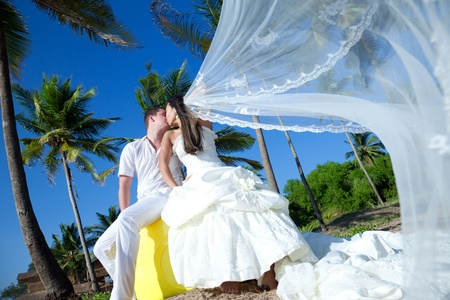 Newlyweds are sharing an intimate moment at an exotic location photo