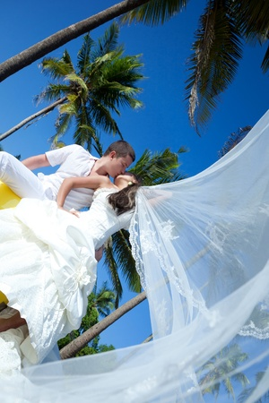 Happy newlyweds kissing in the tropical paradise photo