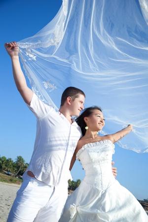Happy newlyweds on the beach photo