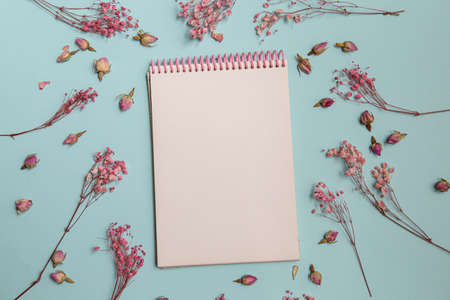 Top view of mock up blank old notebook with single flower, decorated with dry sprigs of flowers on light background. copy space for handwriting calligraphic letter