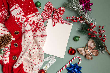 Creative mockup made of Christmas toys, tree branches and sweaters with blank notepad. Christmas and New Year theme.