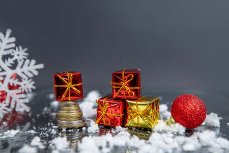 coins, christmas ball, small gifts on gray blurred background, christmas decoration