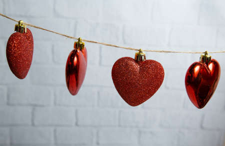 red hearts hang on a thread on a white brick background. High quality photo 版權商用圖片