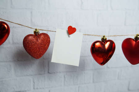 red hearts and white card hang on a thread on a white brick background. High quality photo 版權商用圖片