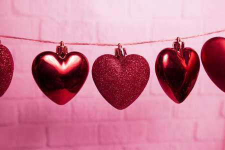 red hearts hang on a thread on a pink background. High quality photo 版權商用圖片
