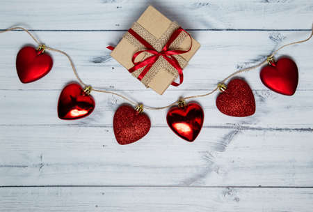 red hearts with gift box on a light wooden background. valentines day. High quality photo