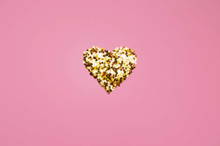 shiny heart made of sequins on a pink background. valentines day. High quality photo