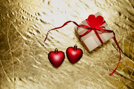 red hearts with gift box on a golden background. valentines day. High quality photo