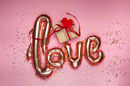 golden word love with gift box on pink background. High quality photo