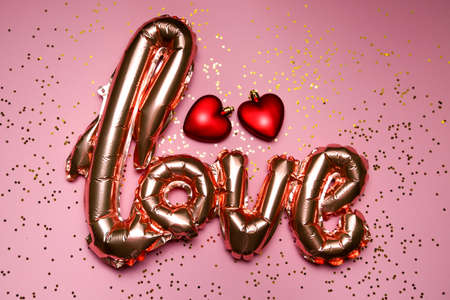 golden word love with red hearts on pink background. High quality photo