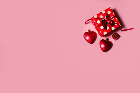 red gift box with hearts on a pink background. High quality photo