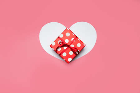 Gift box and heart on a pink background. High quality photo