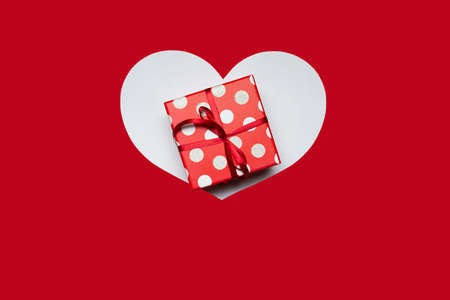 Gift box and heart on a red background. High quality photo