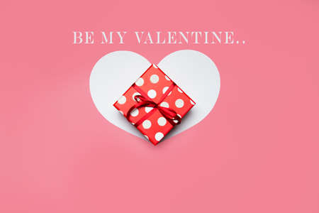 Gift box and heart on a pink background, be my valentine text. High quality photo