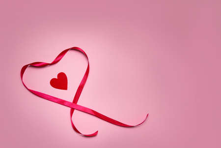 heart made of red ribbon on a pink background. Valentines Day. High quality photo