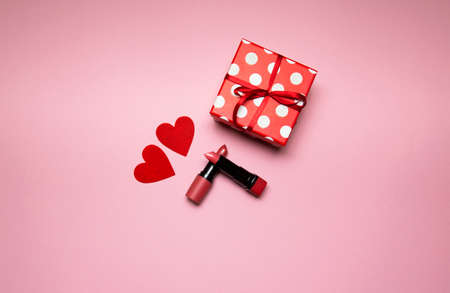 lipstick with a gift box and small heart on pink background. High quality photo 版權商用圖片
