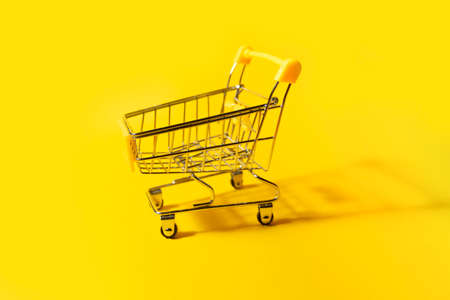 Yellow shopping cart on yellow 版權商用圖片