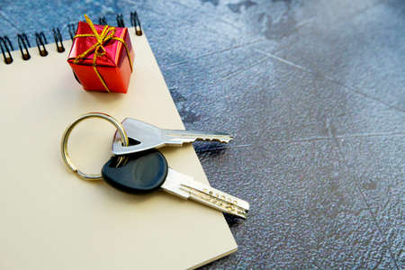 bunch of keys, notepad and a small gift on a gray background. apartment as a gift
