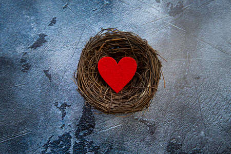 red felt heart in nest on gray background, valentines day background. High quality photo