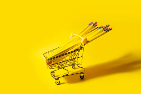 yellow pencils in yellow cart on yellow background. High quality photo