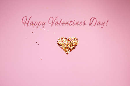 shiny golden heart made of sequins on a pink background. valentines day. High quality photo