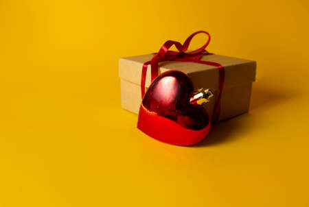 gift with red heart on yellow background. High quality photo