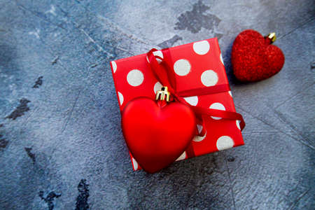 red polka dot gift box with hearts on gray concrete background. High quality photo