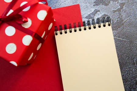 notepad and red gift box on a red-gray background . High quality photo 版權商用圖片