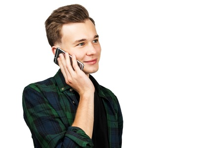 White young guy speaks on the phone and is surprised. Isolated on a white background.