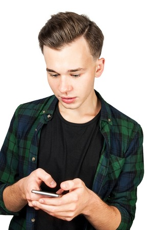 White young guy writes a message on the mobile phone and smiles. Isolated on a white Background. Standard-Bild