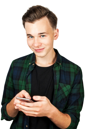 White young guy writes a message on the mobile phone and smiles. Isolated on a white Background.
