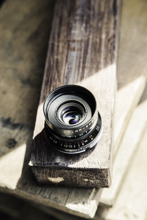 lens unit: lens from film SLR camera lying on old wooden boards Stock Photo